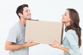Cheerful woman and her husband holding a box women in their new house Royalty Free Stock Photo