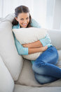 Cheerful woman holding pillow sitting on couch in bright living room Stock Photo