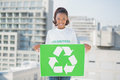 Cheerful woman holding recycling sign outdoors on urban background Royalty Free Stock Image