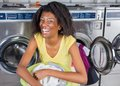Cheerful woman with laundry basket portrait of young sitting at laundromat Royalty Free Stock Photography