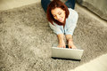 Cheerful woman lying on the carpet and typing on the laptop at home Royalty Free Stock Photography