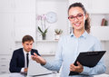 Cheerful woman manager holding cardboard in office