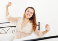 Cheerful woman in nightrobe awaking at home on white her bed Royalty Free Stock Photography