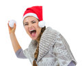 Cheerful woman in Santa hat throwing snowball Stock Photo