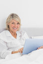 Cheerful woman sitting in bed using tablet pc looking at camera her bedroom home Stock Photos