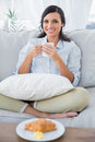Cheerful woman on sofa drinking coffee and having croissant in her living room Royalty Free Stock Photography