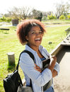Cheerful woman standing hands folded on campus portrait of young university Royalty Free Stock Image