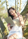Cheerful woman with tablet pc laughing young cheering and sitting on a tree Royalty Free Stock Photos