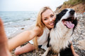 Cheerful woman taking selfie with dog on the beach Royalty Free Stock Photo