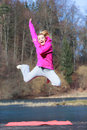 Cheerful woman teenage girl in pink tracksuit jumping outdoor Royalty Free Stock Photo