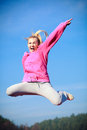 Cheerful woman teenage girl in tracksuit jumping showing outdoor Royalty Free Stock Photo