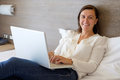 Cheerful woman using her laptop on the bed Royalty Free Stock Photo