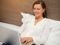 Cheerful woman using her laptop in the bedroom Royalty Free Stock Photo