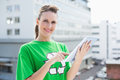 Cheerful woman wearing recycling tshirt using tablet outside Stock Photography