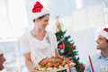 Cheerful woman wearing santa hat and bringing a roast chicken women at christmas dinner Royalty Free Stock Image