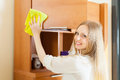 Cheerful woman wiping the dust from wooden furniture blonde at home Stock Photography