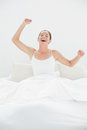 Cheerful woman yawning while stretching arms in bed young her at home Stock Image