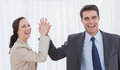 Cheerful workmates doing high five in bright office Stock Image