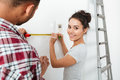 Cheerful yong couple using brush and measuring tape Royalty Free Stock Photo