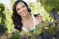 Cheerful young adult woman enjoying a glass of wine in vineyard pretty mixed race the Stock Photos