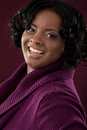 Cheerful young african american woman portrait smiling plus size on dark background Stock Photos