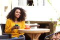 Cheerful young african woman sitting at outdoor cafe Royalty Free Stock Photo
