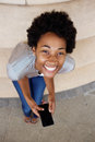 Cheerful young african woman sitting on steps with a mobile phone high angle portrait of and looking up Royalty Free Stock Photo