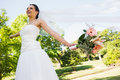 Cheerful young beautiful bride with bouquet in park low angle view of a standing the Royalty Free Stock Image