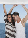 Cheerful young couple dancing on yacht with sea in background Stock Photo