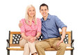 Cheerful young couple posing seated on a bench isolated white background Royalty Free Stock Photo