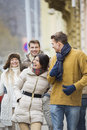 Cheerful young couples in warm clothing on city street Royalty Free Stock Photo