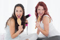 Cheerful young female friends singing into hairbrushes Royalty Free Stock Photo