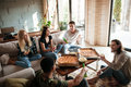 Cheerful young friends eating pizza and talking in living room Royalty Free Stock Photo