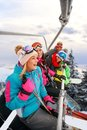 Cheerful friends skiers on ski lift ride up on ski slope at snow