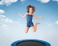 Cheerful young girl jumping on trampoline Royalty Free Stock Photo