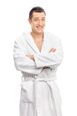 Cheerful young guy posing in a white bathrobe vertical shot of isolated on background Stock Photos