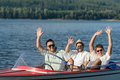 Cheerful young guys in sunglasses partying in speed boat Royalty Free Stock Image