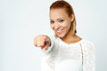 Cheerful young lady pointing you out attractive model towards camera Stock Image