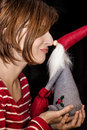 Cheerful young lady touches the nose with Santa Claus by Christmas time Royalty Free Stock Photo
