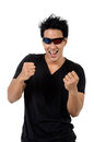 A cheerful young man with clenched fist and wildly smile is enjo in black t shirt d glasses Royalty Free Stock Images