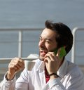 Cheerful young man drinking coffee and talking on mobile phone close up portrait of a Royalty Free Stock Image