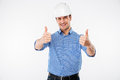 Cheerful young man engeneer in building helmet showing thumbs up Royalty Free Stock Photo