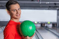 Cheerful young man holding bowling ball at the alley he is a and looking at camera Stock Images