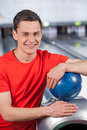 Cheerful young man holding bowling ball at the alley he is a and looking at camera Royalty Free Stock Image