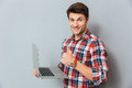 Cheerful young man holding laptop and showing thumbs up Royalty Free Stock Photo