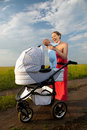 Cheerful young mother taking her baby out of pram Stock Photography