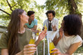 Cheerful young multiethnic friends students outdoors drinking juice Royalty Free Stock Photo