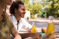 Cheerful young multiethnic friends students outdoors drinking juicee. Royalty Free Stock Photo