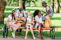 Young multiethnic students holding books and paper cups while sitting on bench and talking in park Royalty Free Stock Photo