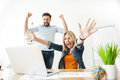 Cheerful young office workers are expressing happiness cute two colleagues celebrating their success they looking at laptop with Stock Images